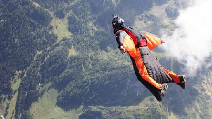 A photo of someone base jumping, which is known as one of the most extreme sports