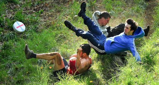 men fall down hill whilst rolling cheese