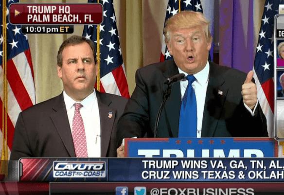 Chris Christie looking sad behind Donald Trump