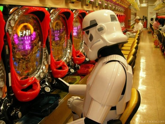 player in storm trooper costume plays a pachinko machine