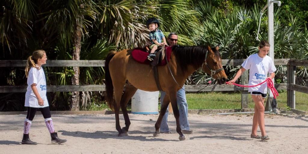 little boy getting a pony ride