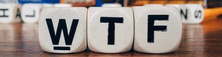 """Close up of three wooden cubes with the letters """"WTF"""""""