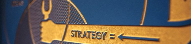 "Gold and blue wall plaque with the word ""strategy"""