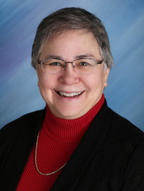 Dr. Elaine Berry in a black jacket and red sweater.