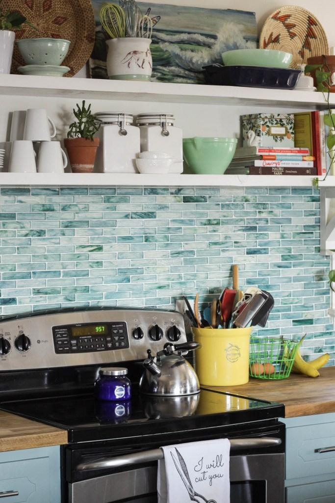 Kitchen with aqua backsplash and cabinets