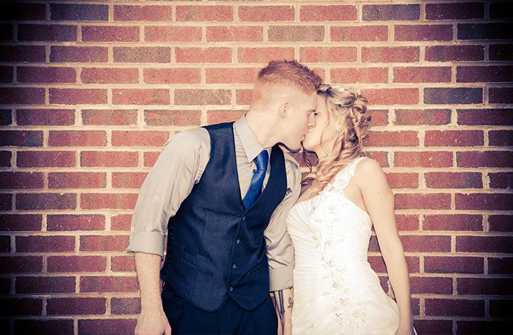 bride-and-groom-kiss-brick-wall