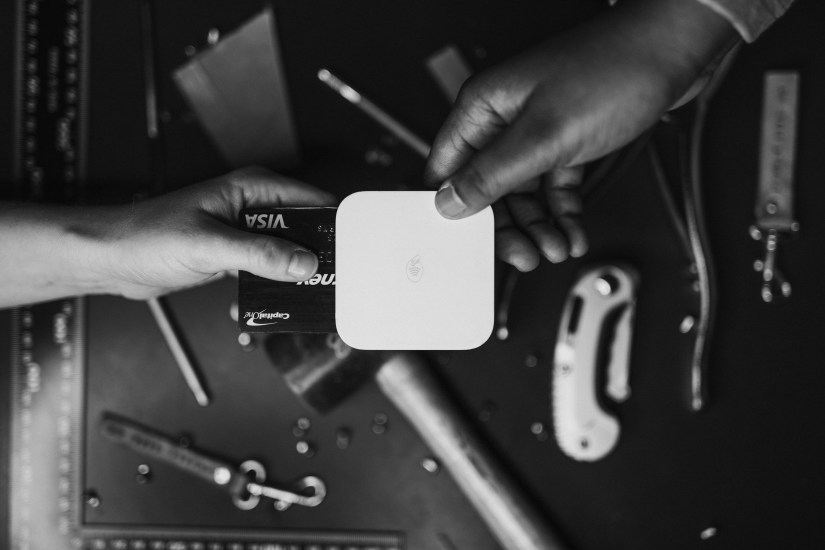 two hands, one putting a credit card in a square reader.