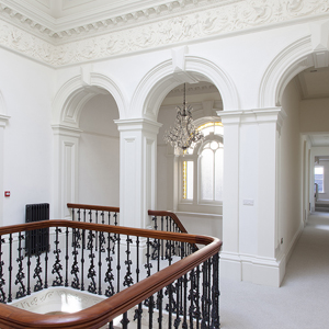 White hallway from a large stately home with cast iron radiator and balustrade in central atrium.