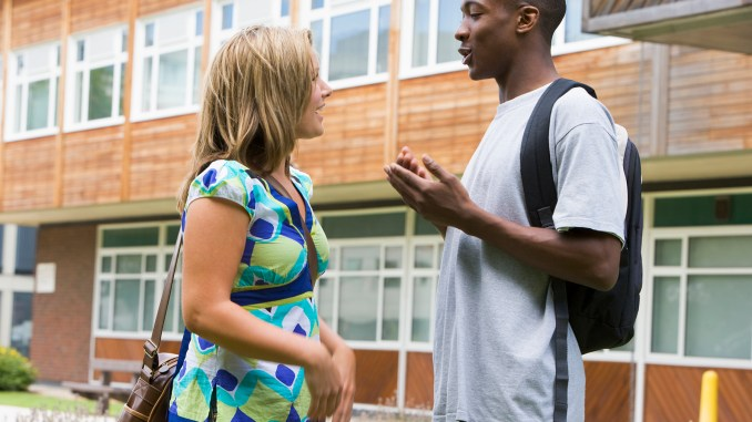 Male and female college students talking on campus image