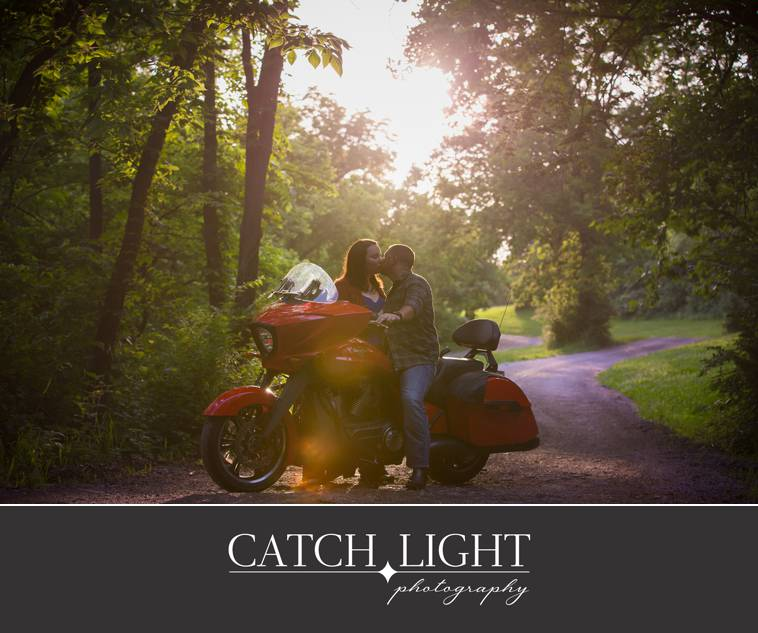 Kansas City engagement photos with a motorcyle and the sun coming through the trees