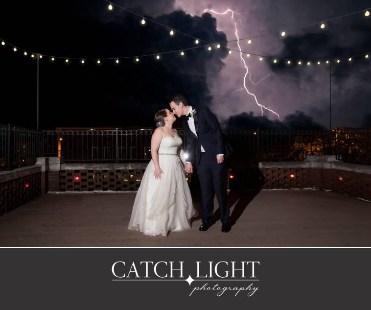 bride and groom with lightning storm behind them