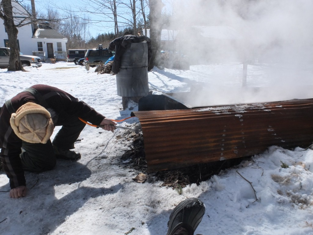 Maple sugaring time - fire under the evaporator is being lit
