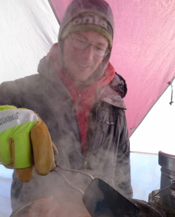 Elliot Gaddy cooking even more bacon on the north fork of the West Fork Glacier, Hayes Range, Alaska.