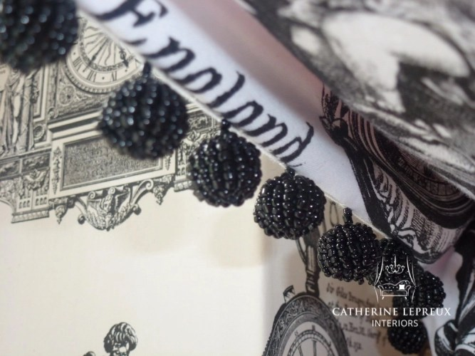 Black bead trimmings on a black and white swagged curtain