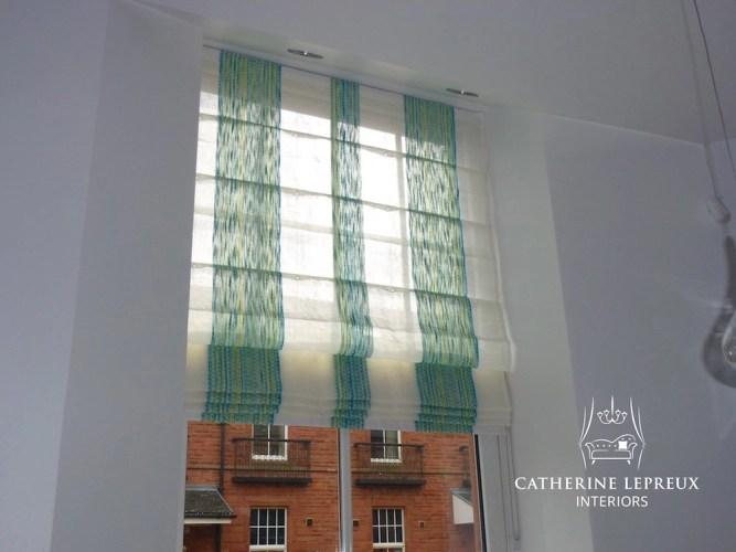 Contemporary green striped linen roman blind at a tall Edinburgh window.