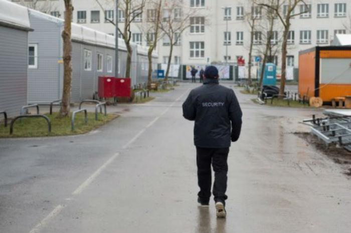 A security guard walks through an emergency shelter for refugees in Germany.