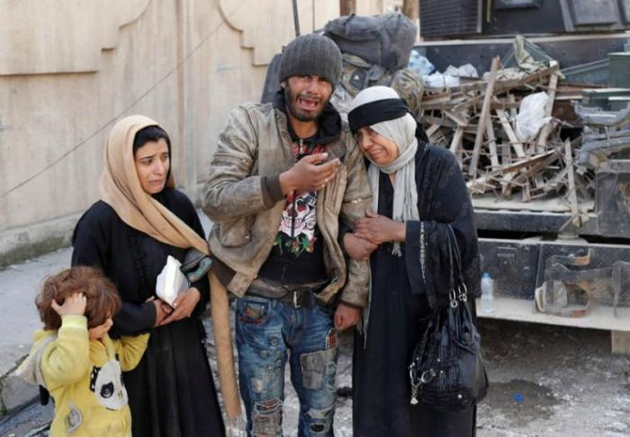 A family trying to escape fighting between Iraqi forces and ISIS fighters cry on a street in Mosul, Iraq.