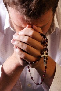 man-praying-with-rosary