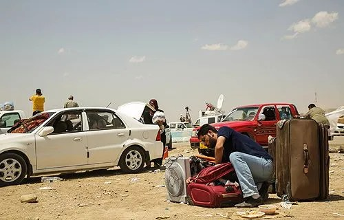 A man leaves his car and packs his bag at the Khazair checkpoint after fleeing from Mosul, Iraq on June 11, 2014. Credit: R. Nuri UNHCR/ACNUR via Flickr (CC BY-NC-SA 2.0).