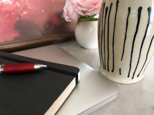 Computer, notebook, flowers, coffee mug