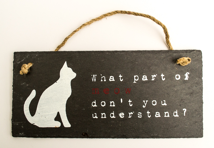 Black plaque with a white cat and 'What part of meow don't you understand' written on it