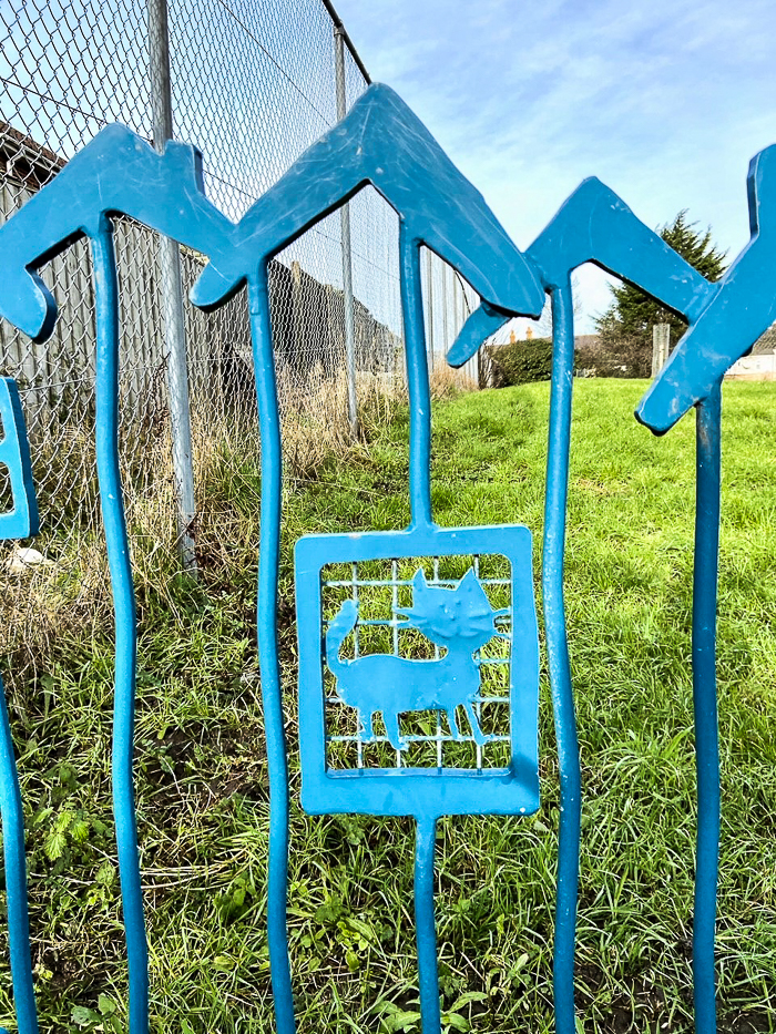 Blue metal railings with an image of a cat in a square