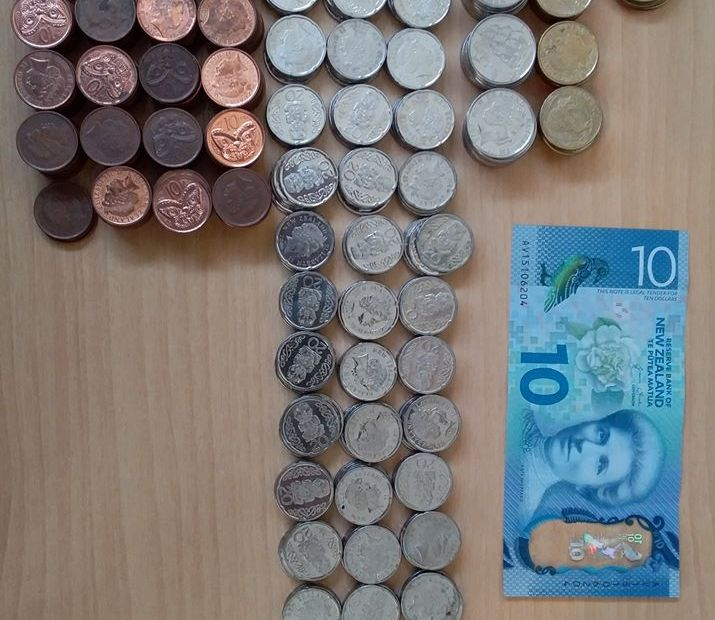 Rows of coins, sorted into piles. A $10 note is beside them.