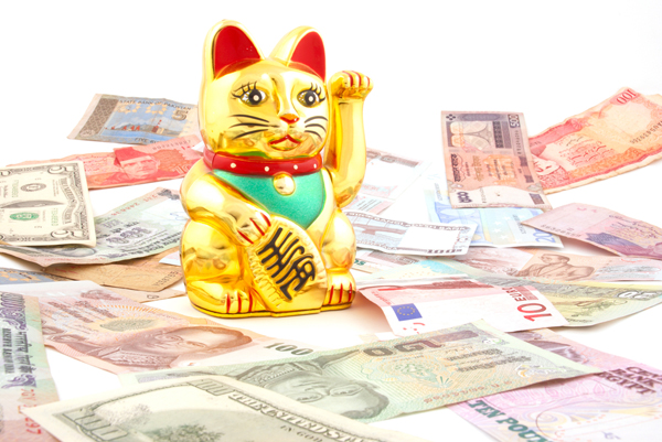 A Maneki Neko, or lucky cat, surrounded by money.