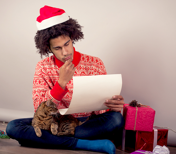 A man looks at his holiday list while wrapping gifts.