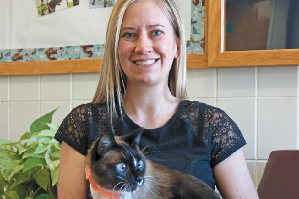 Dr. Alycen Lundberg with her first clinical cat patient, Smokey.