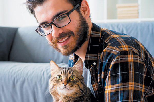 Professional man or guy with glasses holding a cat.