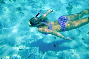 girl snorkeling below on a private boat charter in grand cayman
