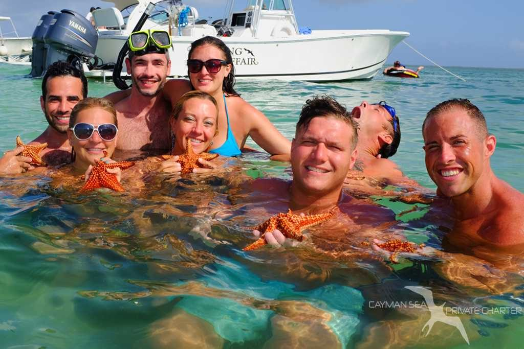 group of friends on a private charter at starfish point grand cayman