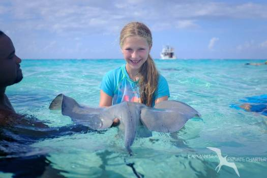 young girl enjoy holding a baby stingray at stingray city grand cayman