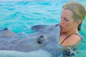 woman kissing a stingray on a private boat charter to stingray city grand cayman