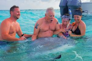 family laughing with a stingray in their arms on a private boat charter in grand cayman