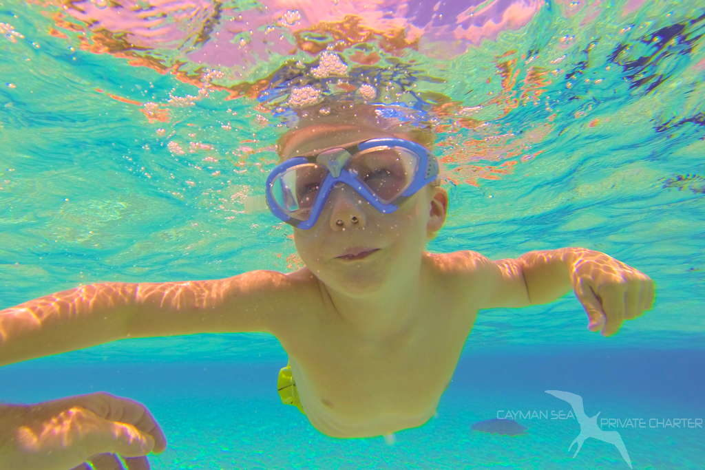 young boy swimming at stingray city on a private boat charter in grand cayman