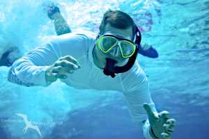 man swimming down to the camera on a snorkeling tour in grand cayman
