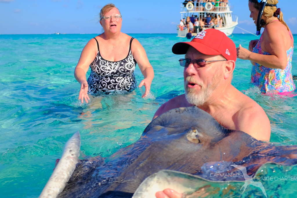 man holding a stingray having fun at stingray city grand cayman