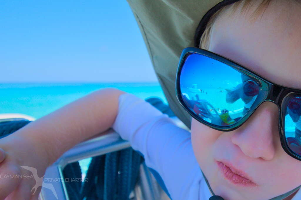 boy with stingray city grand cayman reflected in his sunglasses