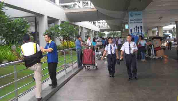 Departing passengers outside Ninoy Aquino International airport terminal