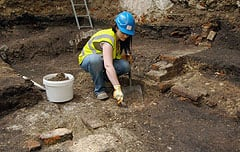 An archeologist works on uncovering the remains of The Theatre. (Museum of London/Associated Press)