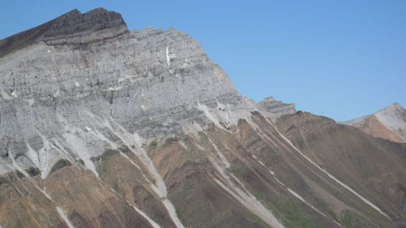 In this Yukon mountain, a maroon-coloured, iron-rich layer of glacial deposits 716.5 million years old can be seen on top of older, grey carbonate reef.