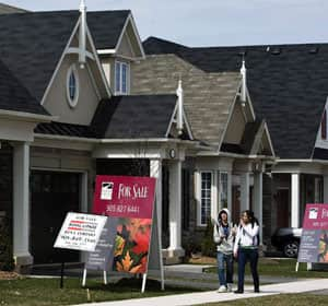 People walk past new homes that are for sale in Oakville, Ont., on Tuesday. Federal mortgage rules implemented two months ago aimed at turning down the heat on Canada's red-hot real estate market took effect Monday.