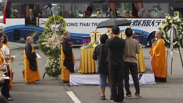Relatives of one of the eight hostages killed in a bus siege pay their respects during a Buddhist religious ceremony, at the site of the hostage taking in Manila, Philippines, on Tuesday.