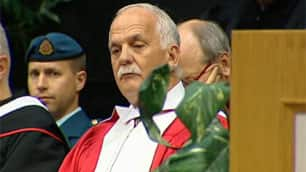 Federal Public Safety Minister Vic Toews looks down as valedictorian Erin Larson speaks at the fall graduation ceremony.
