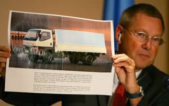 Detlev Mehlis, the German judge who was the UN commission's first chief investigator, holds up a photo in June 2005 of a white Mitsubishi truck, like the one that housed the 1,000 kg bomb that killed Hariri. (Jamal Saidi/Reuters)