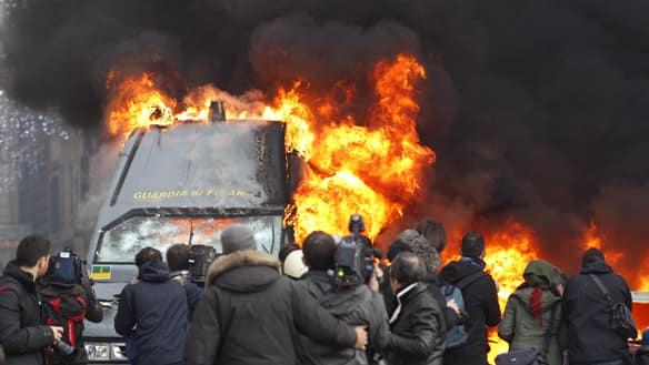 Protesters in Rome torch cars after Italian Prime Minister narrowly survived two confidence votes Tuesday.