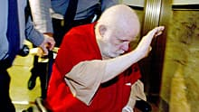 In this Feb 9, 2004, file photo, Kenneth Parnell, 72, tries to block his face from cameras as he is escorted from Alameda County Superior Court in Oakland, Calif.