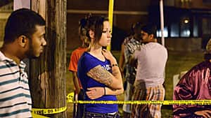 Pedestrians early Tuesday look at the scene of a shooting in Toronto's east end that left 22 people injured and two dead at a house party late Monday.